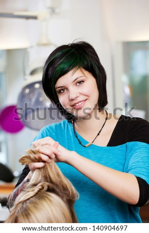 portrait of a smiling young woman working in salon - stock photo