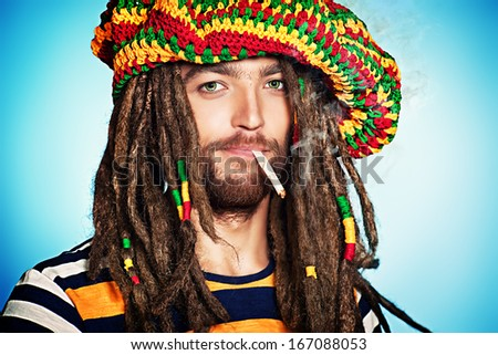 Portrait of a smoking rastafarian young man. - stock photo