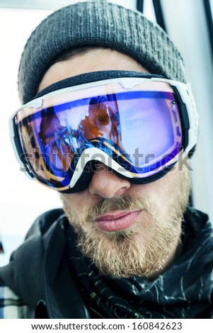 Portrait of a snowboarder with a beard in winter resort in sunglasses mask at ski resort in mountains. Reflection of the photographer - stock photo
