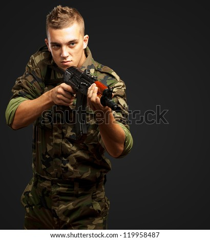 Portrait Of A Soldier Aiming With Gun against a black background - stock photo
