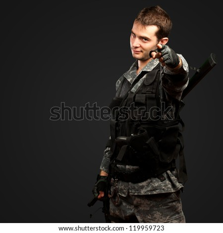 Portrait Of A Soldier Pointing against a black background - stock photo