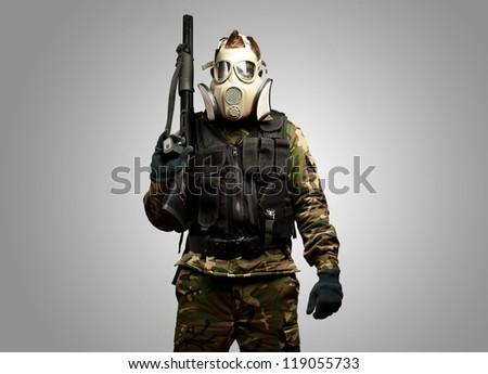 Portrait Of A Soldier With Gas Mask against a grey background - stock photo