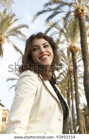 Portrait of a sophisticated young woman walking down a palm trees avenue, turning around. - stock photo