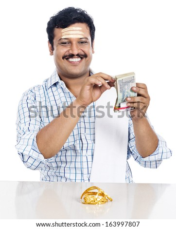 Portrait of a South Indian man counting money and smiling - stock photo