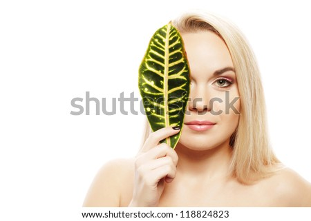 Portrait of a spa woman. Beautiful blonde girl after bath hides a half of her face with a leaf of plant. Perfect skin. Skincare. Young skin. Studio shot - stock photo
