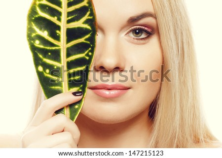 Portrait of a spa woman. Beautiful blonde girl after bath hides a half of her face with a leaf of plant. Perfect skin. Skincare. Young skin. Close up. Studio shot - stock photo