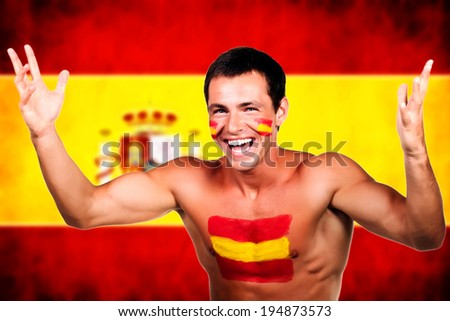 Portrait of a spanish soccer fan over spain flag background - stock photo