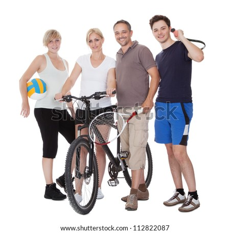 Portrait of a sporting family each holding their equipment of choice with a volley ball - stock photo