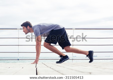 Portrait of a sports man in start position outdoors. Reading for run - stock photo