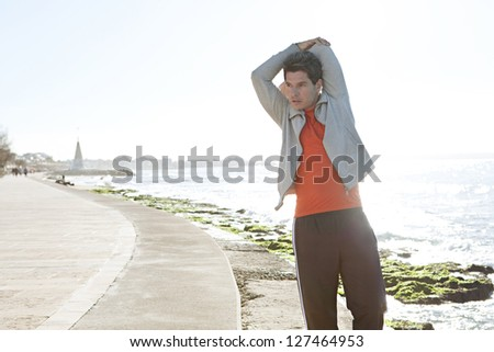 Portrait of a sports man stretching his arms after exercising by the sea, next to the water, against a blue sky background. - stock photo