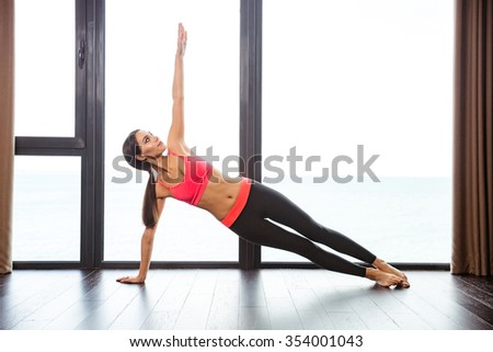 Portrait of a sports woman doing yoga exercises in fitness gym - stock photo