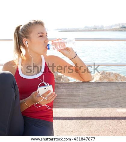 Portrait of a sporty adolescent girl exercising, using a smart phone and headphones, drinking bottle of mineral water by the sea, coastal outdoors. Fitness and sport lifestyle, sunny exterior. - stock photo