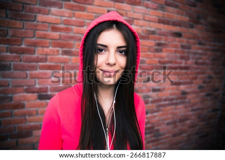 Portrait of a sporty woman in headphones over brick wall - stock photo