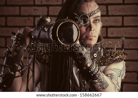 Portrait of a steampunk man with a mechanical devices over brick wall. - stock photo
