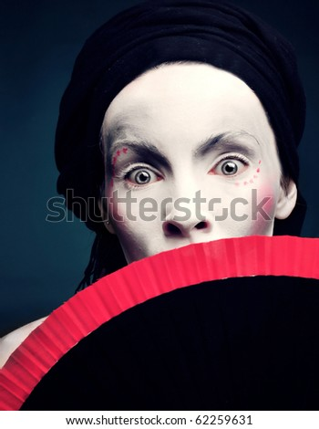 portrait of a strange woman mime or a clown with a fan and bodypainting - stock photo