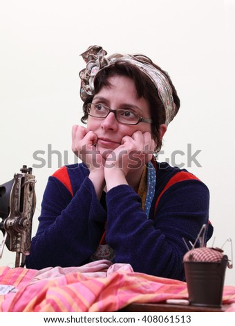 Portrait of a streamstress at her workplace in the workshop. - stock photo