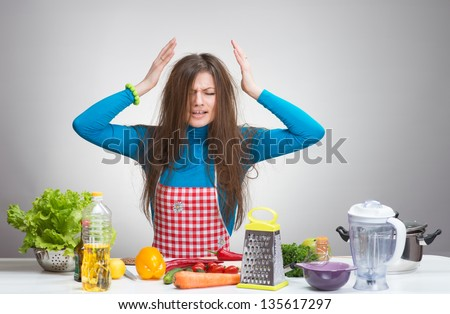 Portrait of a stressed housewife in the kitchen - stock photo