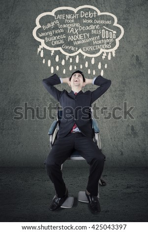 Portrait of a stressful handicapped entrepreneur sitting on the wheelchair while thinking his problems - stock photo