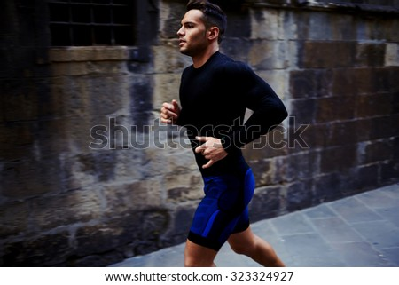 Portrait of a strong fit men dressed in sportswear jogging on the street in summer day, young athletic male running outdoors, handsome sportsmen engaged in physical exercise in the fresh air  - stock photo