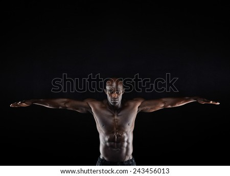 Portrait of a strong young muscular man stretching his arms against dark background. Afro-american man showing off his physique. - stock photo