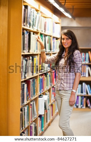 Portrait of a student choosing a book while looking at the camera - stock photo