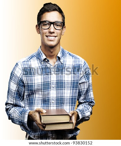 portrait of a student holding books and smiling against an orange background - stock photo