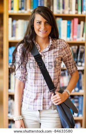 Portrait of a student holding her bag in a library - stock photo
