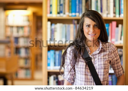 Portrait of a student posing in a library - stock photo