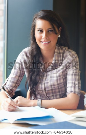 Portrait of a student working in a library - stock photo