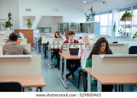 Portrait of a students studying in library - stock photo