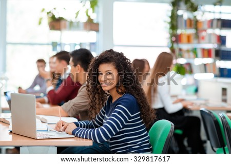 Portrait of a students studying in university library - stock photo