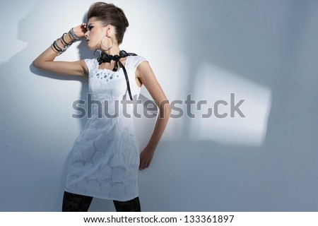 portrait of a styled professional model wearing modern sunglasses on light background - stock photo