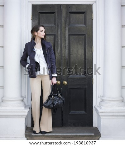 Portrait of a stylish caucasian woman standing by a black door. Business or lifestyle image. - stock photo
