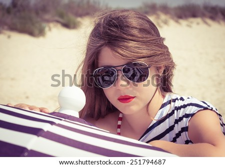 Portrait of a stylish girl in a striped t-shirt and sunglasses by a beach umbrella - stock photo