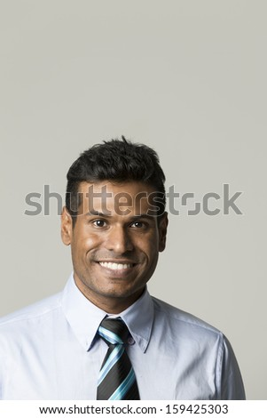 Portrait of a stylish Indian businessman standing in front of a light grey background. The photo has been composed so there is plenty of space for your message. - stock photo