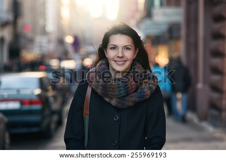 Portrait of a Stylish Pretty Young Woman in Autumn Fashion walking the city Looking at the Camera. - stock photo