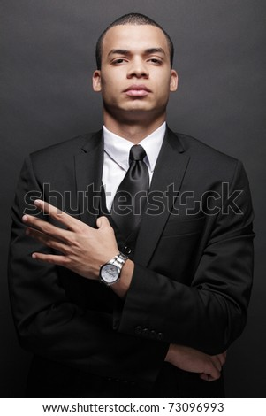 Portrait of a stylish young businessman in a black suit. - stock photo