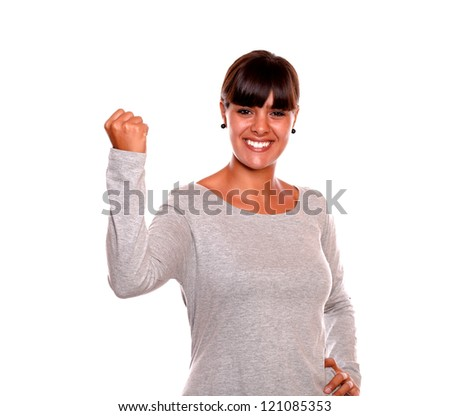 Portrait of a stylish young woman celebrating and looking at you standing over white background - stock photo