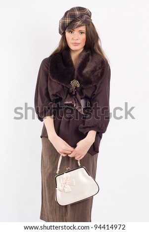 Portrait of a stylish young woman in a jacket with a fur collar and cap. Fashion photos. - stock photo