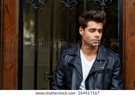 Portrait of a stylishly-dressed young man standing in the street against wooden door, handsome fashionable male in trendily clothing posing outdoors in the city - stock photo