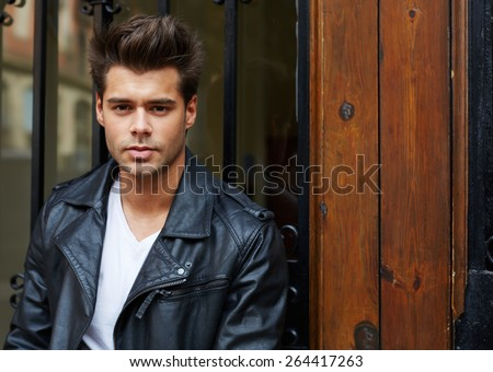 Portrait of a stylishly-dressed young man standing in the street, handsome fashionable male in trendily clothing posing outdoors in the city - stock photo