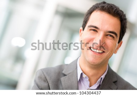 Portrait of a successful businessman looking happy - stock photo