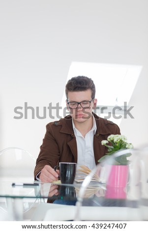 Portrait of a successful businessman sitting at his desk, looking camera in office - stock photo