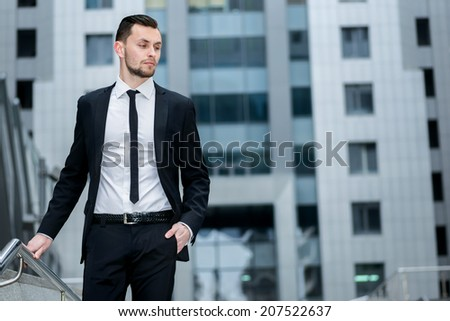 Portrait of a successful businessman. Successful businessman walks down the stairs and looking away. - stock photo