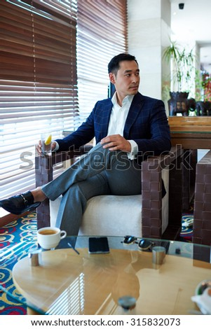 Portrait of a successful managing director enjoying a drink while waiting for a business partners in cozy restaurant, handsome men entrepreneur with serious face looking aside while relaxing in cafe - stock photo