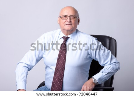 portrait of a successful senior man on gray background - stock photo