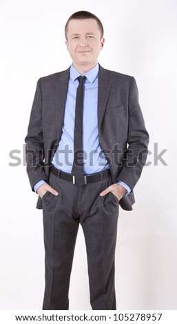 Portrait of a successful young business man with hands in pockets smiling. - stock photo