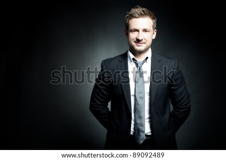 Portrait of a successful young business man with his hands folded on a dark background - stock photo