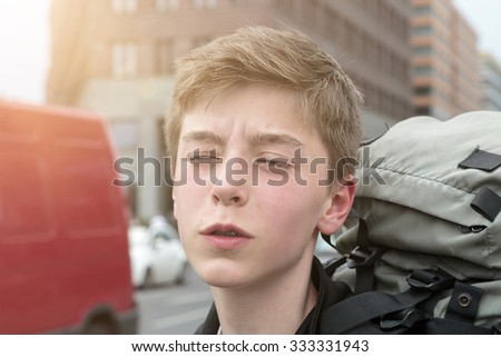 portrait of a suffering teenage boy with heavy backpack - stock photo