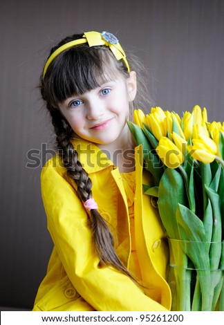 Portrait of a sunny child girl with bouquet of yellow tulips on a dark background - stock photo